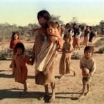 Indigenas maes e filhos caminham